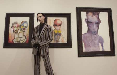 Gothic rock musician Marilyn Manson poses in front of three of his original paintings during a private reception at the Los Angeles Contemporary Exhibitions in Hollywood September 19, 2002. The art 
